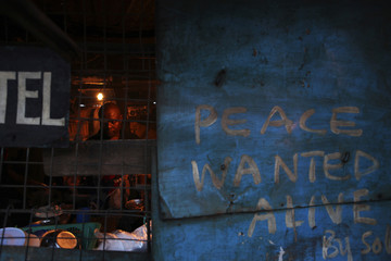 A man works in a hotel with its wall painted with graffiti in Kibera slum in the capital Nairobi