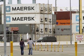 Union members walk a picket line during a strike near APM Terminals in Los Angeles