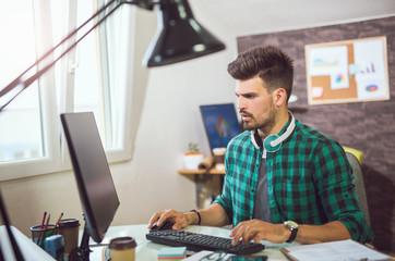 Handsome Caucasian man at work desk facing flat screen computer in office