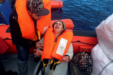 Nadia, 42, from Morocco cries while praying next to her son Sofian, 24, following a rescue operation by the Spanish NGO Proactiva Open Arms in the central Mediterranean Sea, 18 miles north of the coastal Libyan city of Sabratha