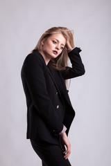 Styled blonde in fashion suit on gray background in studio photo. Elegant blonde