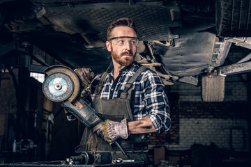 Mechanic in protective googles holds angle grinder. Wall mural