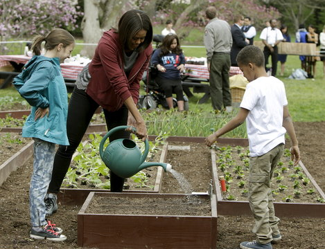 United States first Lady Obama waters freshly-planted vegetables with school children during spring planting of the White House vegetable garden in Washington