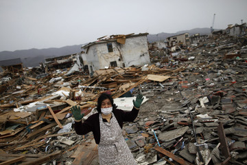 Ichiko Hirayama tells about her experience as she stands in the ruins of her home in the destroyed residential part of Ofunato