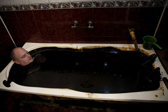 A man lies in a bathtub filled with crude oil during a health therapy session in Naftalan health centre in Baku