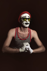 Portrait of mime wearing red hat and yellow eyeglasses