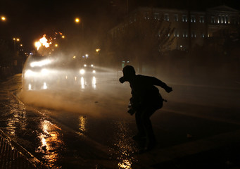 Protestor throws a molotov cocktail at a riot police water cannon during a 48-hour strike by the two major Greek workers unions in central Athens