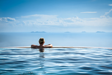 Woman relaxing in infinity swimming pool looking at view