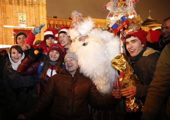 Revellers pose for a picture with a man dressed as Father Frost, the equivalent of Santa Claus, during celebrations of New Year's Day in Red Square in Moscow