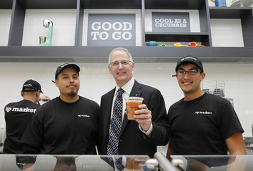 Walgreens CEO and President Wasson holds a fruit smoothie as he poses for a picture at the juice bar in Hollywood