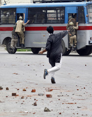 A Kashmiri protester throws pieces of bricks at an Indian police bus during a clash in Srinagar