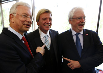 Koch outgoing CDU Prime Minister of the German state of Hesse and Hahn party leader of the FDP point towards Koch's designated successor Bouffier in Wiesbaden