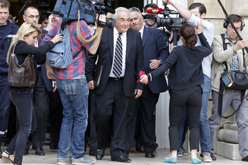 Former International Monetary Fund chief Dominique Strauss-Kahn is surrounded by journalists as he leaves the French Senate in Paris