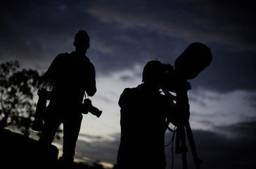 Photographers wait under cloudy skies to capture a glimpse of the Super Moon at twilight on Sydney Harbor