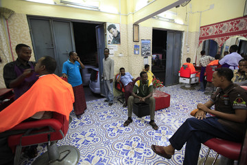 Men receive haircuts at a barber shop in Mogadishu