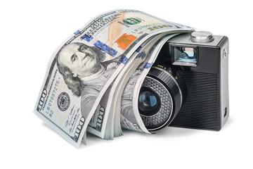 Old retro camera with a bundle of money lying on it, isolated on a white background