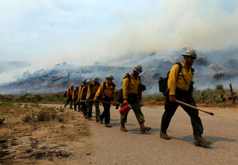 U.S. Forest Service firefighters walk to their truck after battling a wildfire near Potrero