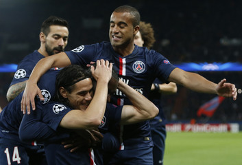 Paris St Germain's Cavani celebrates with team mates after he scored the first goal for the team during their Champions League soccer match against APOEL Nicosia at the Parc des Princes in Paris