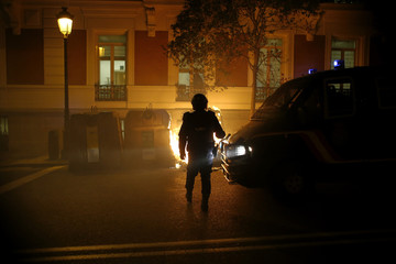 A riot police officer looks at a fire in Madrid, during a demonstration in support of protesters in Burgos opposing an urban project