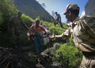 A woman is helped by soldiers to climb down a hill during a rescue operation at Govindghat in the Himalayan state of Uttarakhand
