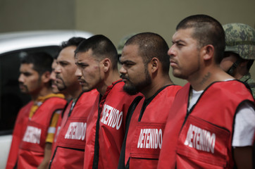 Soldiers escort detainees during a presentation to the media at the State Investigative Police headquarters in Monterrey
