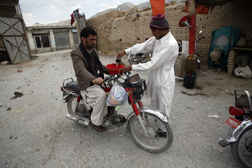 A man fills the tank of a motorbike with petrol, which he says was brought from Iran, at a roadside shop in Quetta
