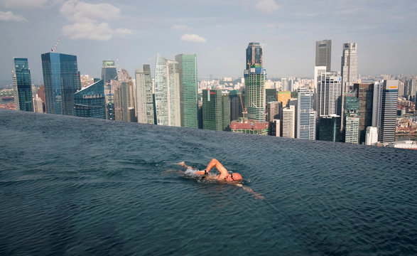 A guest swims in the infinity pool of the Skypark that tops the Marina Bay Sands hotel towers in Singapore
