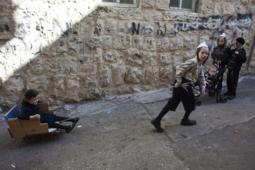 An ultra-Orthodox Jewish boy pulls a girl on a cart in Jerusalem's Mea Shearim neighbourhood