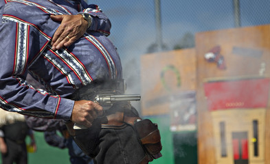Lawton of Deadwood, South Dakota fires his single action revolver after cocking the gun with his left hand during the Canadian Open Fast Draw Championships in Aldergrove