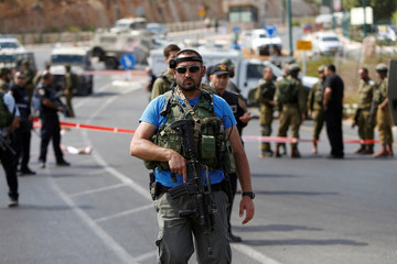 Israeli security forces gather at the scene of what the Israeli military said was a car ramming attack by a Palestinian near the Jewish settlement of Kiryat Arba near the West Bank city of Hebron