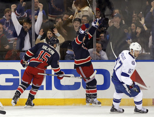 New York Rangers' Asham and Halpern celebrate behind Tampa Bay Lightning's Pouliot after Asham scored in their NHL game in New York