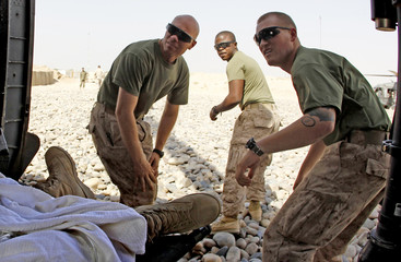 US Marines wait for all clear from the medevac crew after dropping off an Afghan soldier suffering abdominal pains near the town of Marjah