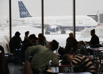 People wait in the food court as snow continues to accumulate during a 'Nor-Easter weather pattern bringing blizzard conditions to Laguardia airport, in New York