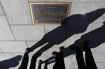 The shadows of people standing for a minute's silence are cast on the ground at the unveiling of the Titanic Memorial Garden in Belfast's City Hall