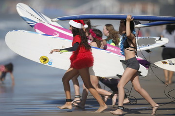 Competitors run into the ocean during the ZJ Boarding House Haunted Heats Halloween Surf Contest in Santa Monica