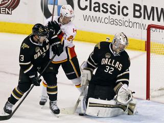 Dallas Stars' goaltender Kari Lehtonen looks for the puck as Stephane Robidas and Calgary Flames' Jiri Hudler stand near during NHL game in Dallas, Texas