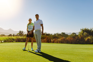 Male and female golfers at field on sunny day