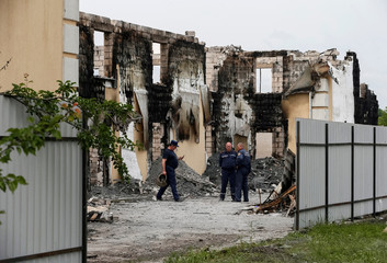 Firefighters work in a burned residential building housing elderly people after a fire broke out, in the village Litochky near Kiev