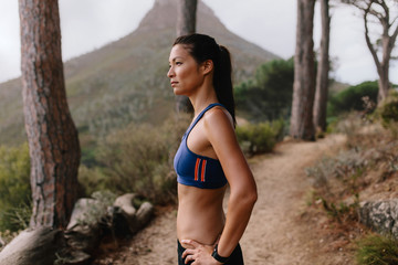Fit young asian woman standing on mountain trail