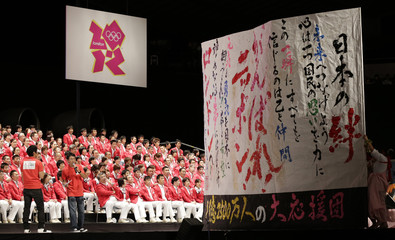 Calligraphic messages of support for Japan's Olympics team are pictured in front of the team members during a send-off ceremony for the team's departure to the London 2012 Olympic Games in Tokyo