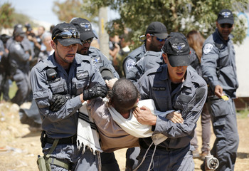 A Jewish settler is carried away by Israeli police officers after they removed him from a structure in outpost near Ramallah