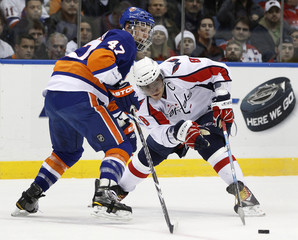 Washington Capitals Alex Ovechkin reaches for the puck as the New York Islanders Andrew MacDonald defends during the first period of their NHL hockey game in Uniondale