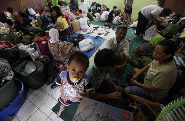Residents who lost their homes to Monday's fire stay in a temporary shelter, a classroom of a school, in Jakarta