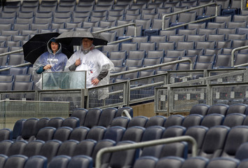 Toronto Blue Jay fans stand in the rain while waiting for the New York Yankees and the Blue Jays MLB American League baseball game in New York