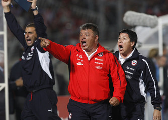 Chile's head coach Borghi celebrates with his staff after their team's second goal against Paraguay during their 2014 World Cup qualifying soccer match in Santiago