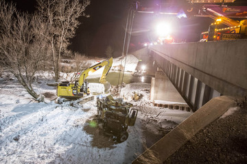A crane prepares to hoist the cab of a truck which left Highway 401 and plunged into a river near Woodstock
