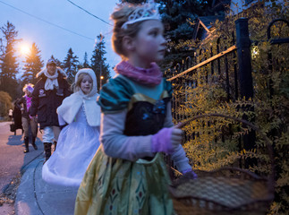 Prime Minister-designate Justin Trudeau, dressed as Han Solo, looks on as youngsters including his daughter Ella-Grace, go trick-or-treating on Halloween in Ottawa