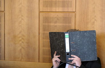 A man identified as Olaf H. hides his face behind a book before being sentenced for murder in District Court in Krefeld