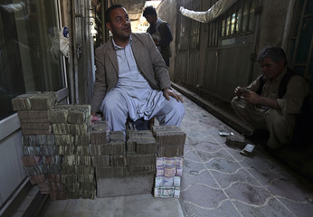 An Afghan money changer sits behind stacks of Afghan currency at Kabul's largest money market