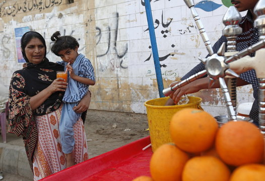 A woman holds a glass orange juice for her daughter to drink next to a cart along a road in Karachi, Pakistan